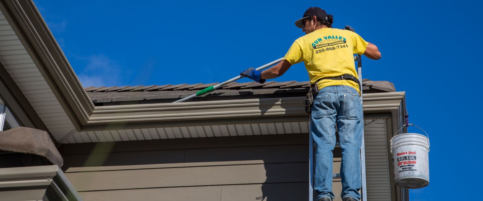 Commercial gutter cleaning in Kelowna from an extension ladder