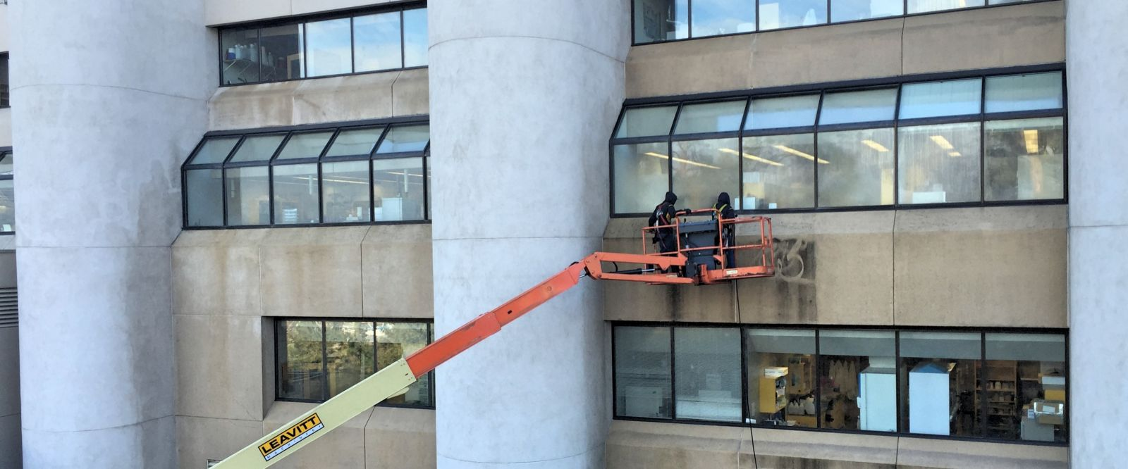 Two technicians pressure washing commercial building in Summerland